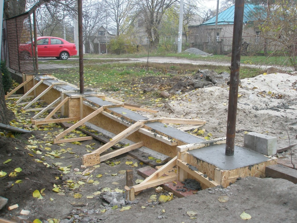 Фундамент ограждения с замоноличенными в нём металлическими стойками
