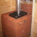 Металлическая печь для бани, обложенная кирпичом до трубы
